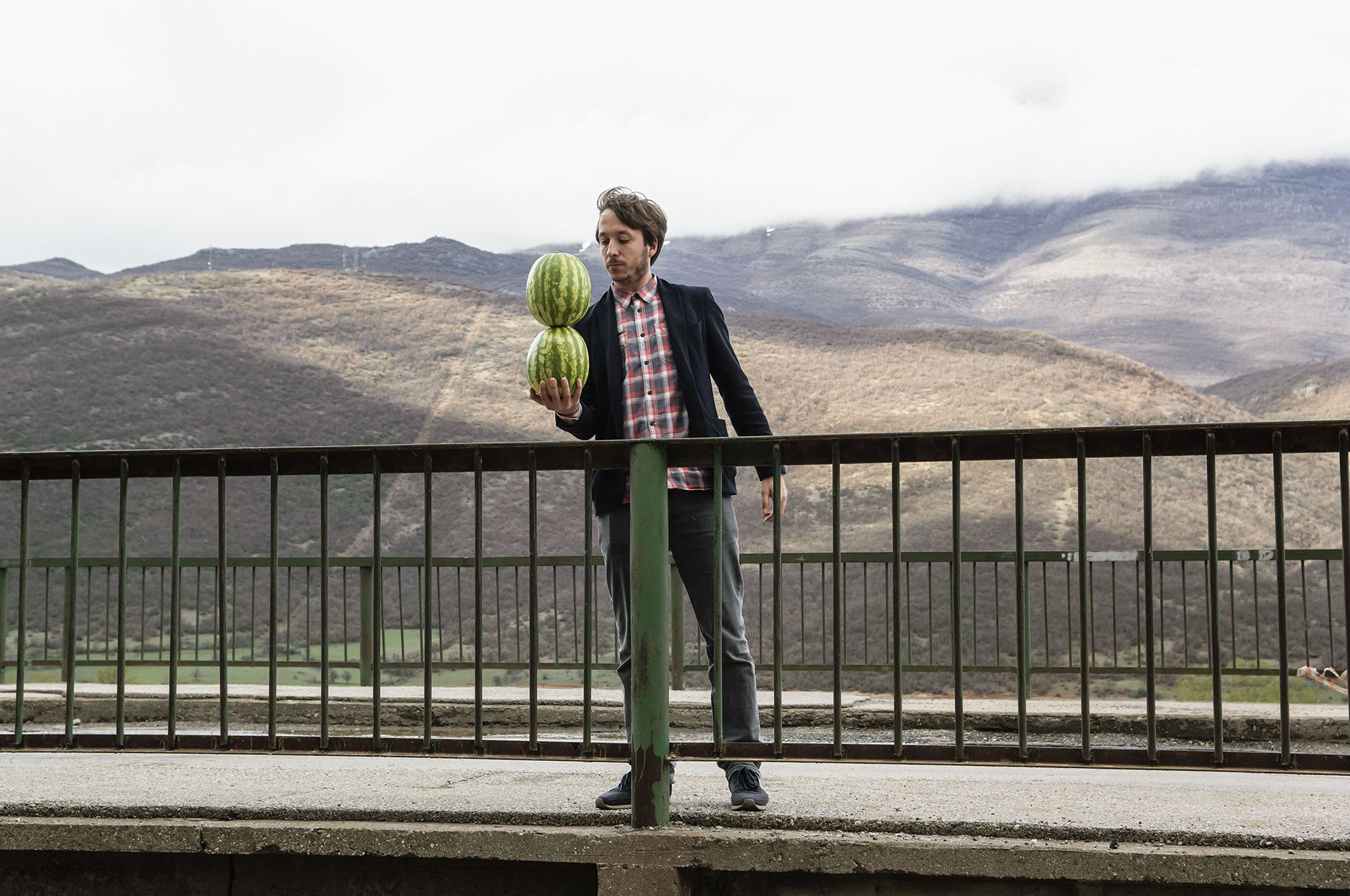 A photograph of a man stood on a bridge in front of hills in sunlight balancing two watermelons in his hand - Driton SELMANI - They say you can't hold two watermelons in one hand