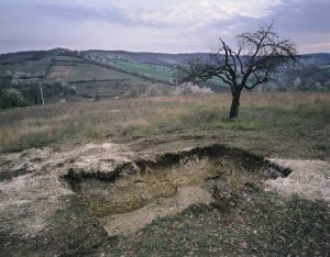 Photograph of a shallow hole in the ground, in a rural landscape with hills in the background and a tree