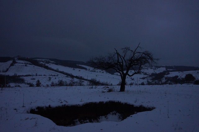 Photograph - dusk, in the snow - of a shallow hole in the ground, in a rural landscape with hills in the background and a tree
